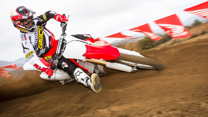 Front 3-quarter view of CRF250R leaning into corner with rider. Dirt track location.